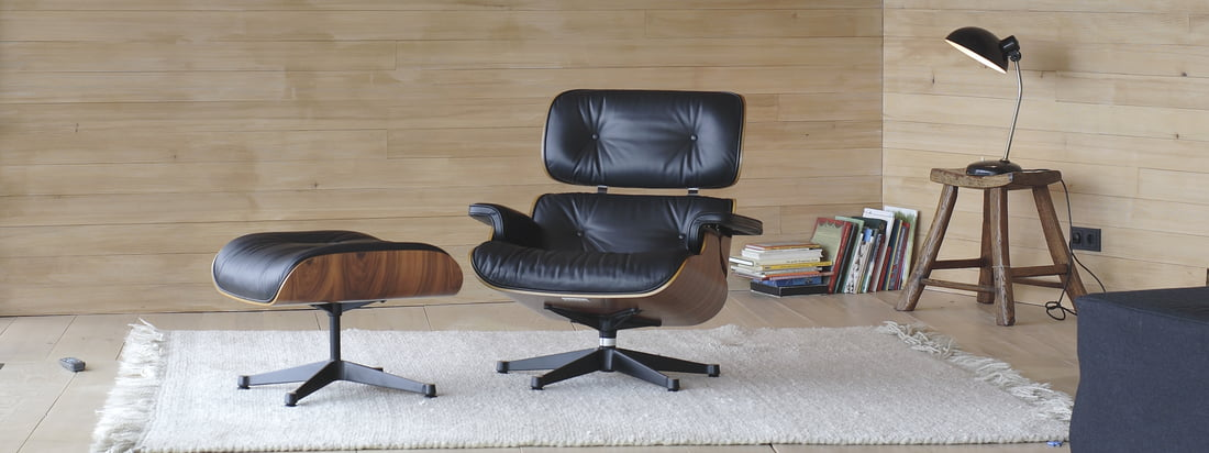 The Vitra Eames Lounge Chair by Charles & Ray Eames with ultimate comfort and highest quality in material and finish. The armchair in dark veneer and black leather is now also available in walnut/white.