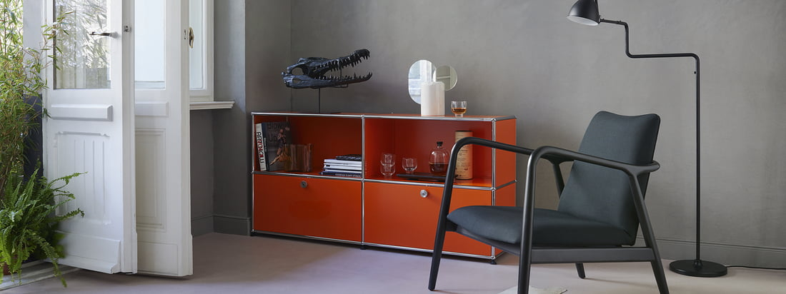 USM Haller - Manufacturer's range - living room - Sideboard M - orange - armchair - floor lamp - books - glasses - white doors - plants - ambience