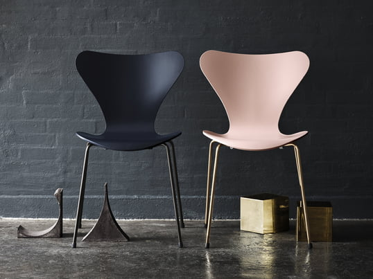 The anniversary edition of the Series 7 chair by Arne Jacobsen: pink seat and gold-plated legs, dark blue seat and powder coated legs (front image)